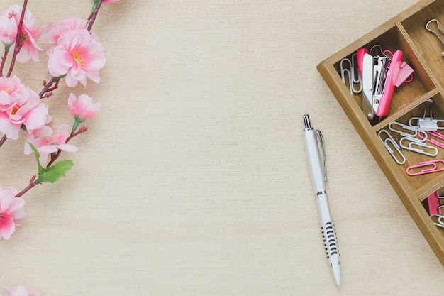 Top view business office desk background.the silver pen coffee beautiful pink flower wood shelf staple clip on wooden table backgtound with copy space. Free Photo