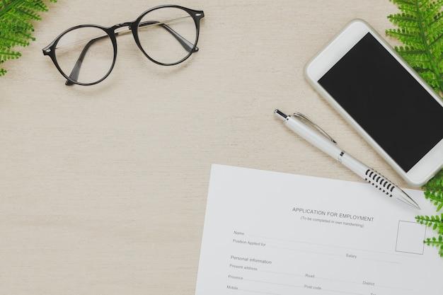 상위 뷰 비즈니스 사무실 책상 배경. 작업 양식 및 펜 연필 안경 나무 휴대 전화 복사 공간 나무 테이블 배경에 적용. 무료 사진