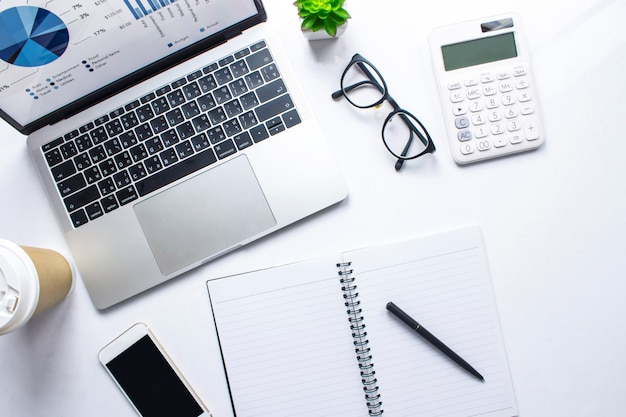 Top view of a business woman desk with financial account information in a laptop on a white table Premium Photo