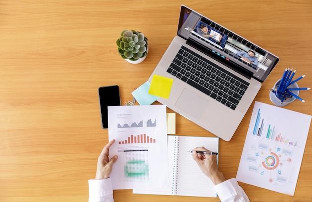 Вид сверху бизнесмен и бизнес-леди анализ финансовой диаграммы с видеоконференцией онлайн-встречи. Premium Фотографии