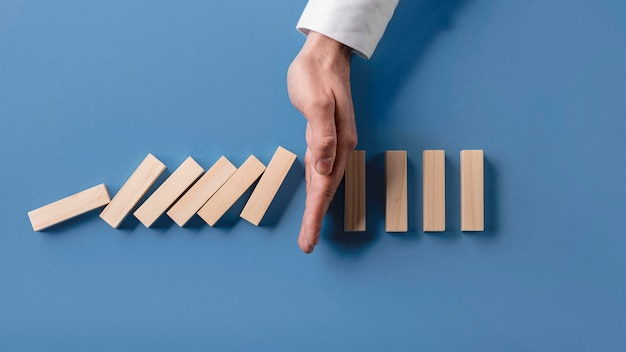 Top view of businessman stopping domino effect Premium Photo