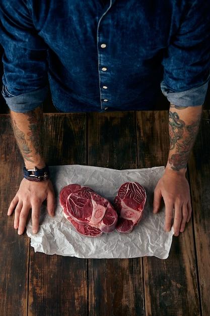 Vista dall'alto delle mani del macellaio e delle bistecche su carta artigianale Foto Gratuite