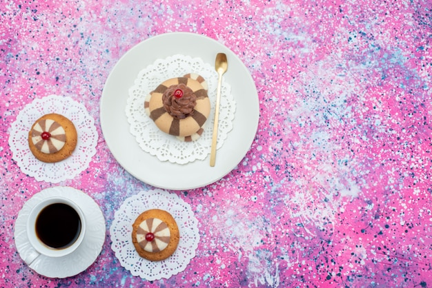 トップビューケーキと色付きの背景のコーヒーカップと共にクッキークッキーケーキ色砂糖 無料写真