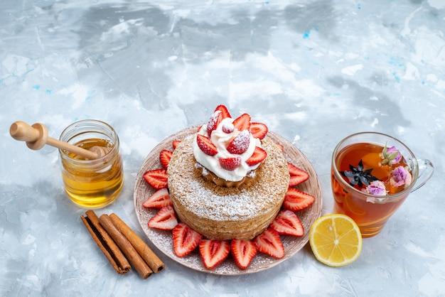 Una fetta di torta vista dall'alto con fragole rosse fresche crema all'interno del piatto con tè sullo sfondo grigio-blu Foto Gratuite
