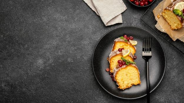 Vista dall'alto di fette di torta sulla piastra con frutti di bosco e copia spazio Foto Gratuite
