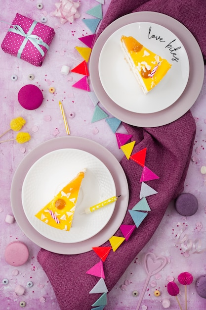 Top view of cake slices on plates with present and garland Free Photo