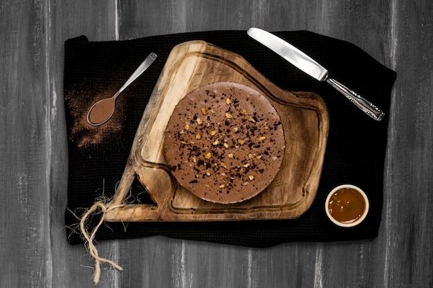 Vista dall'alto della torta con salsa al cioccolato e coltello Foto Gratuite