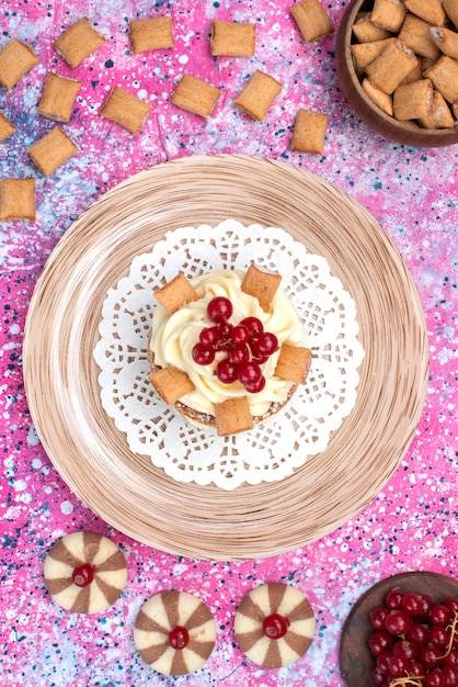 カラフルな背景のケーキビスケットシュガー甘い色のクッキーとクランベリーと一緒にクリームとトップビューケーキ 無料写真