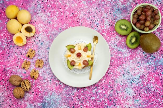 アプリコットとキウイと一緒にクリーム色とフルーツのスライスとトップビューケーキ、色付きの背景のケーキビスケット甘い砂糖の色 無料写真