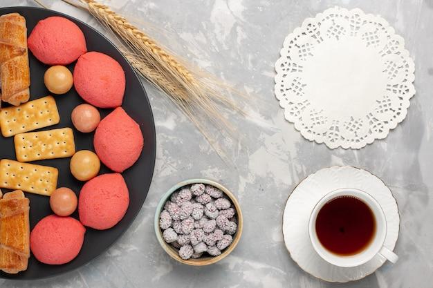 ライトホワイトの背景のプレートの内側にキャンディーとクラッカーが付いた上面図のケーキとベーグルケーキビスケットクッキーシュガースイートパイ 無料写真