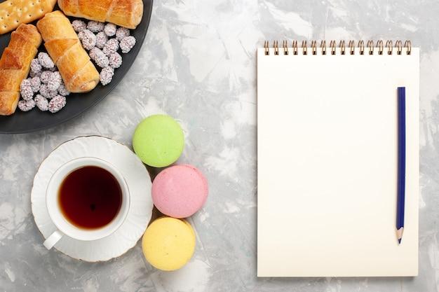 ライトホワイトの背景にキャンディクラッカーとお茶のトップビューケーキとベーグルケーキビスケットクッキーシュガースイートパイ 無料写真