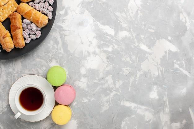 キャンディクラッカーと白い机の上のお茶のトップビューケーキとベーグルケーキビスケットクッキーシュガースイートパイ 無料写真