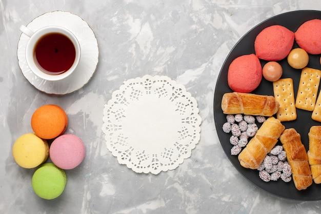 トップビューケーキとキャンディークラッカーマカロンと白い背景の上のお茶のカップケーキビスケットクッキーシュガー甘いパイ 無料写真