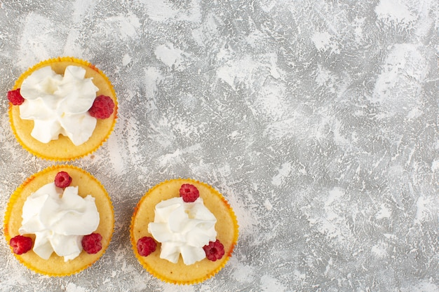 Vista dall'alto torte con crema al forno buonissimo progettato con lampone su sfondo grigio crema di biscotti dolci cuocere Foto Gratuite