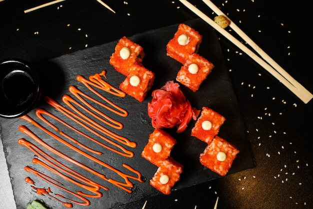 トップビューカリフォルニアロール醤油生姜と醤油を箸でスタンドに 無料写真