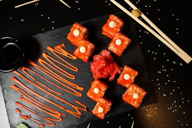 Rotoli di california vista dall'alto con salsa di zenzero e salsa di soia su un supporto con le bacchette Foto Gratuite