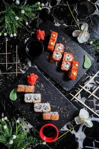 Rotoli di sushi della california di vista superiore con i rotoli di philadelphia sui supporti con wasabi della salsa di soia e zenzero con i fiori Foto Gratuite