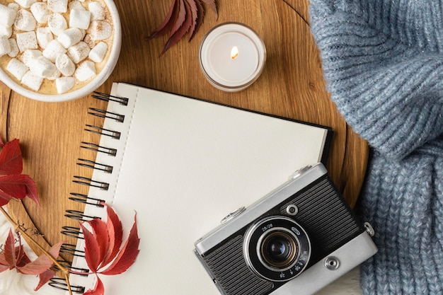 Top view of camera and notebook with cup of hot cocoa with marshmallows Free Photo