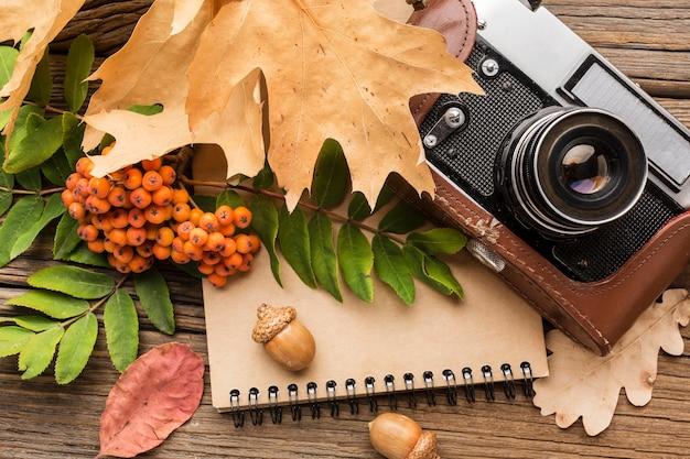 Камера вид сверху с блокнотом и листьями Бесплатные Фотографии