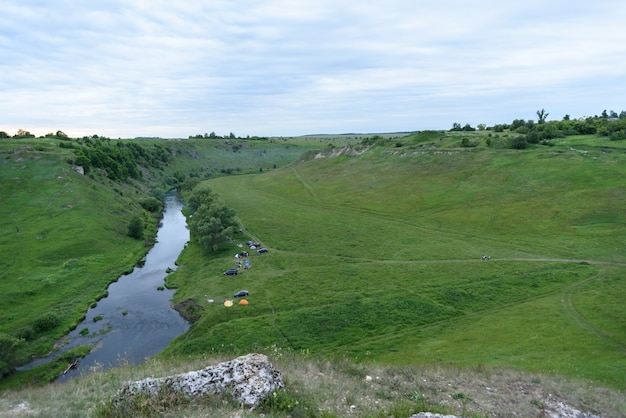 Top view of the camping near a small river with cars and tents, tourism concept Premium Photo