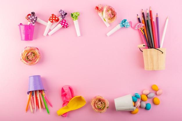 Una vista dall'alto candele e matite insieme a palline e caramelle dappertutto la caramella rosa della foto di colore della decorazione della scrivania Foto Gratuite