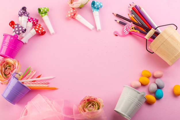 A top view candles and pencils along with flowers and candies on the pink desk brithday color decor photo Free Photo