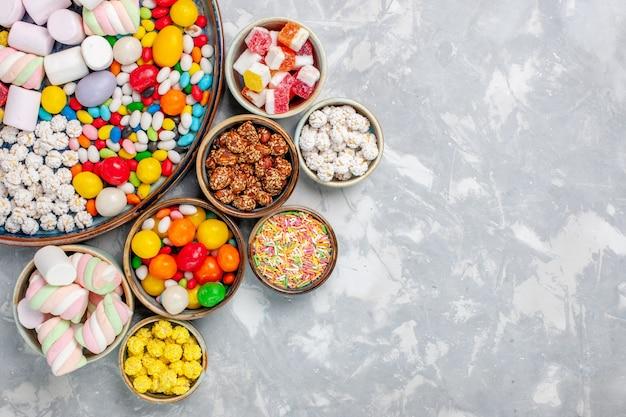 上面図キャンディー組成物甘くておいしいキャンディーとマシュマロを白い机の上に砂糖菓子コンフィチュールスイート 無料写真