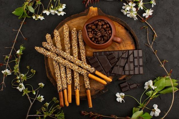 Вид сверху леденцы шоколадные кофейные семена на коричневом столе и темные Бесплатные Фотографии