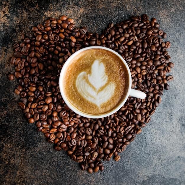 심장의 형태로 상위 뷰 카푸치노 컵과 커피 콩 무료 사진