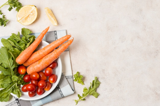 Top view of carrots and tomatoes on plate Free Photo