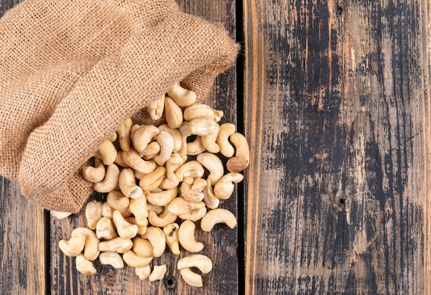 Top view cashews in sack on wooden table Free Photo