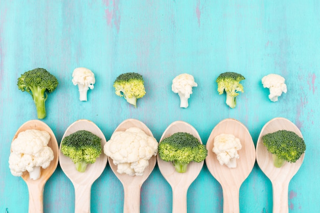 Top view cauliflower and broccoli in wooden spoon on blue surface Free Photo