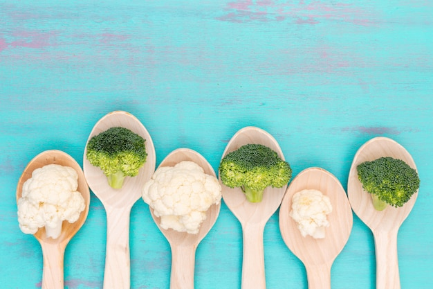Top view cauliflower and broccoli in wooden spoons with copy space on blue surface Free Photo