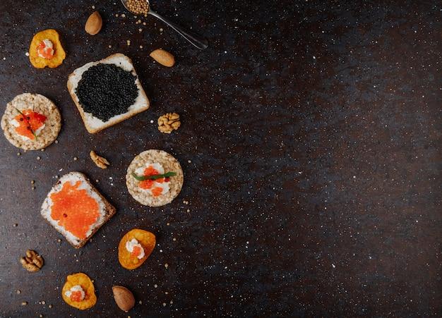 Vista dall'alto antipasti di caviale toast patatine fritte e croccante pane croccante con ricotta caviale rosso caviale nero tarhun mandorle e noci a sinistra con spazio di copia su sfondo nero Foto Gratuite