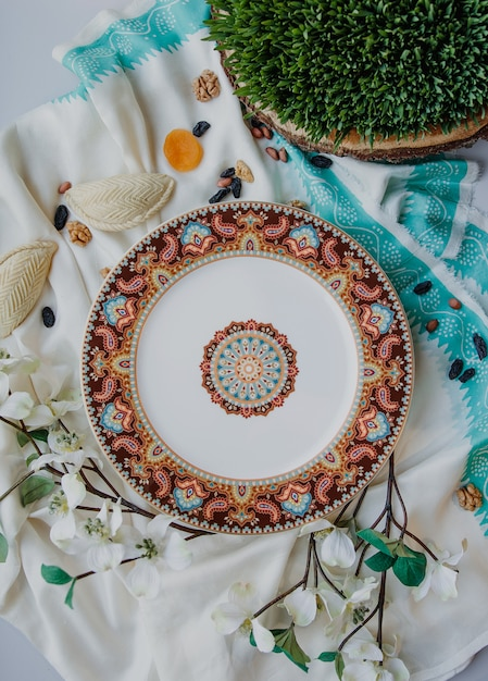 Top view of ceramic eastern plate with a national pattern with shekerbura and semeni on white traditional kelagai silk female scarf wall Free Photo