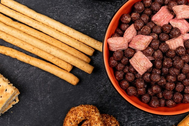Top view cereal balls in plate and bread sticks on dark surface Free Photo