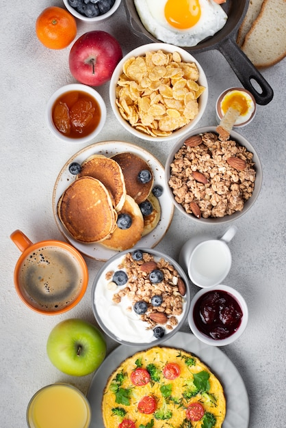 Top view of cereal with omelette and pancakes for breakfast Free Photo