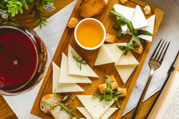 トップビューチーズプレート様々なチーズ、ボード上の蜂蜜のルッコラとクラッカー 無料写真
