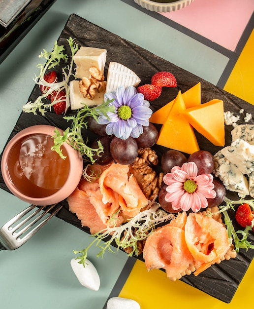 Top view of cheese plate with smoked salmon, blue cheese, cheddar, grape and flowers Free Photo