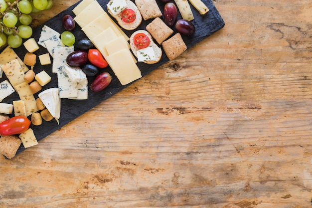 Top view of cheese platters with grapes and tomatoes on table Free Photo