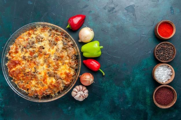 Farina di carne di formaggio vista dall'alto con verdure fresche e condimenti su tavola blu scuro cibo pasto carne piatto cena forno cuocere Foto Gratuite