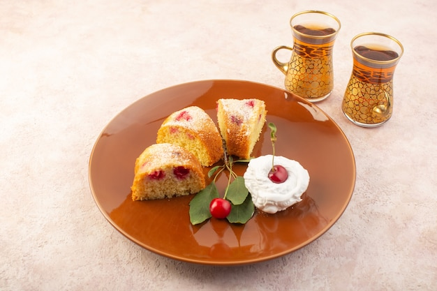 A top view cherry cake slices with cream inside round plate on the pink desk cake biscuit sugar sweet Free Photo
