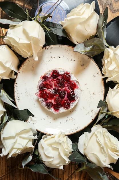 Вид сверху вишневый пирог на тарелке с белыми розами по кругу Бесплатные Фотографии