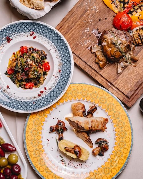 으깬 감자 버섯 상위 뷰 치킨 룰라 드 야채 샐러드와 버섯과 소스와 함께 붉은 고기를 테이블에 구운 무료 사진