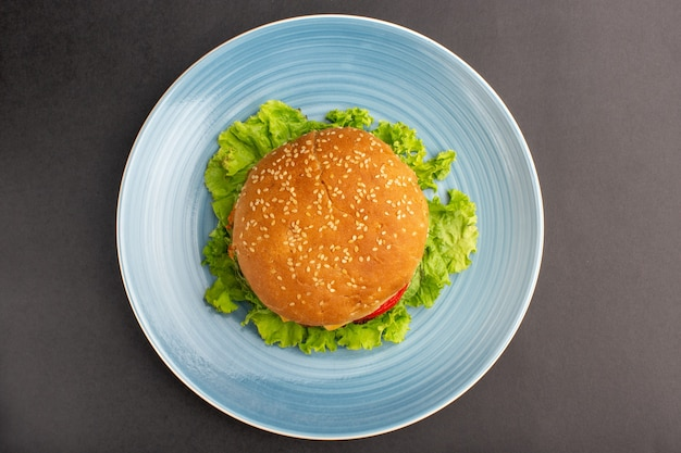 Top view of chicken sandwich with green salad and vegetables inside plate on dark surface Free Photo