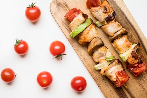 체리 토마토와 함께 커팅 보드에 상위 뷰 닭 꼬치 무료 사진