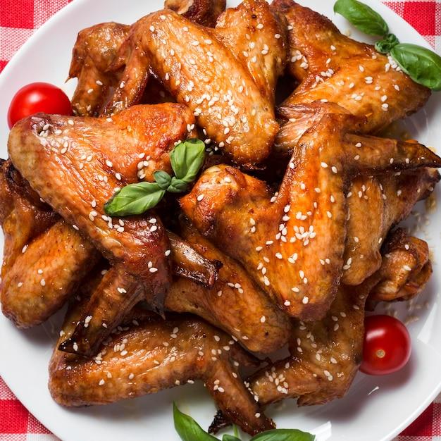 참깨와 체리 토마토와 함께 접시에 상위 뷰 닭 날개 무료 사진
