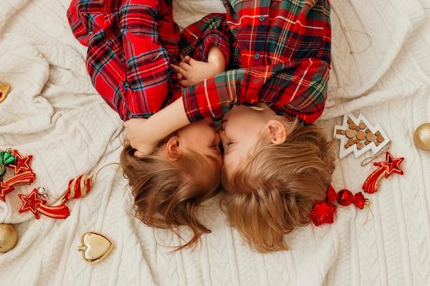 Вид сверху на детей, лежащих в постели на рождество Бесплатные Фотографии