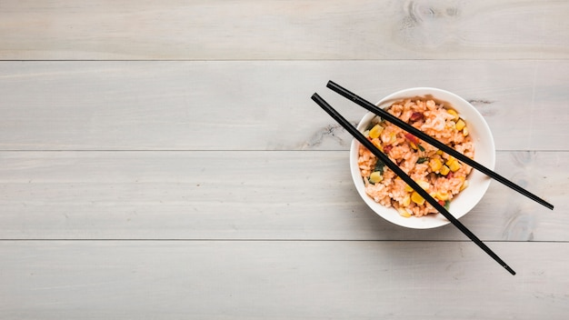 Top view of chinese fried rice bowl with black chopsticks on wooden table Free Photo