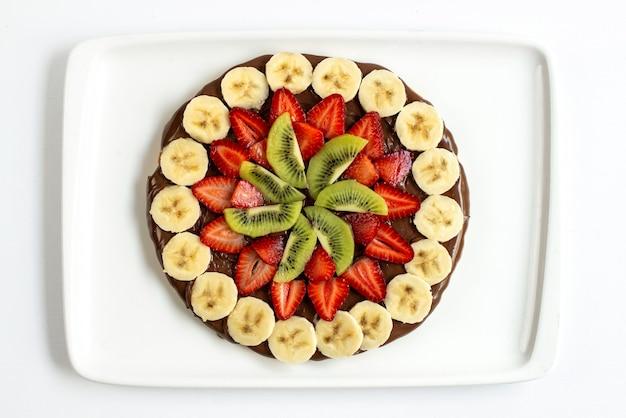 Una vista dall'alto torta al cioccolato con fragole a fette banane e kiwi progettato all'interno della piastra bianca su sfondo bianco festa di compleanno dolce Foto Gratuite